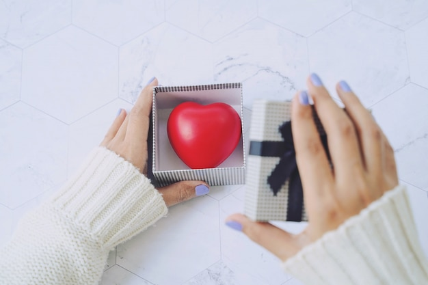 La vista superiore delle mani della donna apre il contenitore di regalo e il cuore rosso dentro il presente