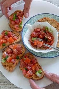 Vista dall'alto delle mani della donna che preparano gustosi antipasti italiani di pomodoro - bruschetta, su fette di baguette tostate, vista ravvicinata