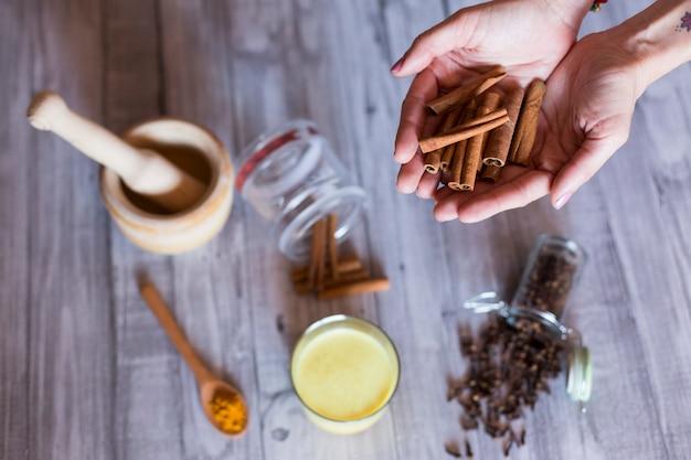 Vista superiore delle mani di donna con ingredienti sul tavolo, mortaio di legno, curcuma gialla, chiodi di garofano e foglie naturali verdi. primo piano, di giorno
