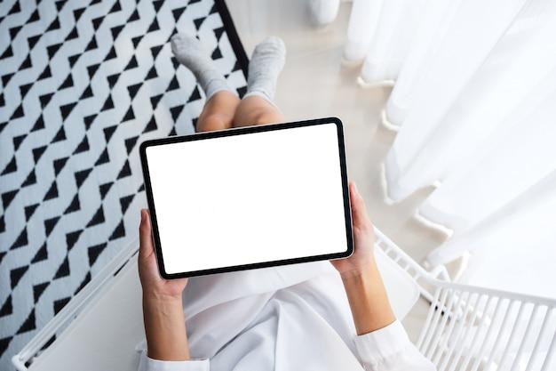 Punto di vista superiore di una donna che tiene il pc nero della compressa con lo schermo da tavolino bianco in bianco mentre sedendosi nella camera da letto con la sensibilità rilassata di mattina