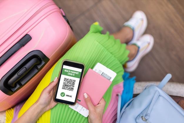 Vista dall'alto donna in possesso di documenti di identificazione certificato immunitario sullo schermo dello smartphone in aeroporto