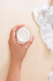 Donna di vista superiore che tiene una crema per la pelle