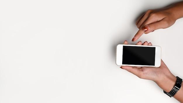 Donna di vista superiore che tiene smart phone con lo schermo in bianco su fondo bianco.
