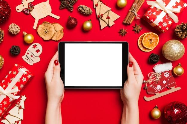 Vista dall'alto della donna che tiene in mano un tablet su sfondo rosso fatto di decorazioni natalizie. concetto di vacanza di capodanno. modello.