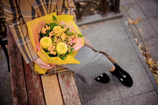 Vista dall'alto della donna in abito lungo e cappotto plaid seduto sulla panchina con un mazzo di fiori gialli