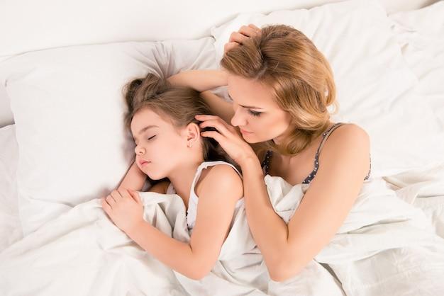 Vista dall'alto della donna che guarda la sua piccola figlia addormentata
