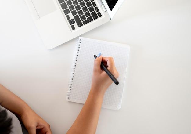 Vista dall'alto della donna che fa la lista della spesa con il laptop