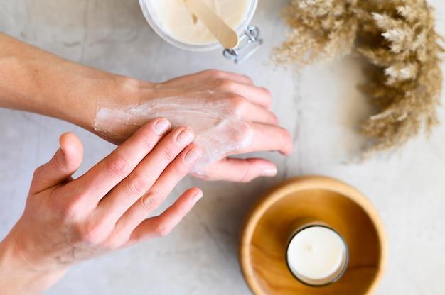 Punto di vista superiore della donna che mette crema sulle sue mani