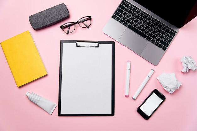 Vista superiore della scrivania rosa della donna con il foglio di carta pulito con lo spazio della copia libera, il computer portatile, il telefono con lo schermo bianco in bianco, una crema, gli occhiali e il fondo dei rifornimenti.