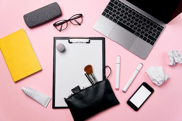 Vista superiore della scrivania rosa della donna con il computer portatile, il telefono con lo schermo bianco, gli occhiali, il rossetto, la crema, la borsa cosmetica e il fondo sgualcito delle palle di carta.