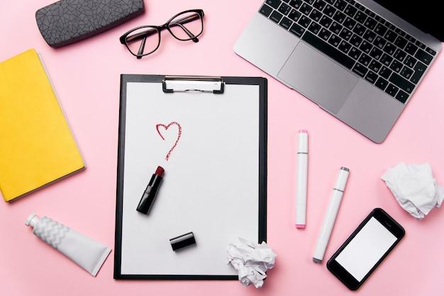 Vista dall'alto della scrivania da donna rosa con laptop, telefono con schermo bianco, occhiali da vista, rossetto, crema e palline di carta stropicciata. amore d'ufficio, il cuore è dipinto di sfondo.