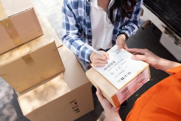 Vista dall'alto della donna che firma per la consegna dei pacchi