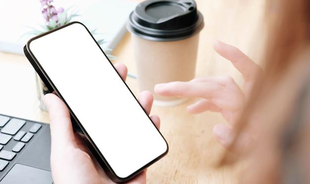 Vista dall'alto donna seduta e tenendo il telefono cellulare con schermo vuoto.