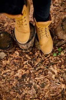 Vista dall'alto donna in piedi con scarponi da montagna su foglie autunnali e fondo in legno