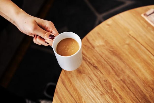 Vista dall'alto della donna che cattura caffè arabica fresca del mattino da un tavolo.