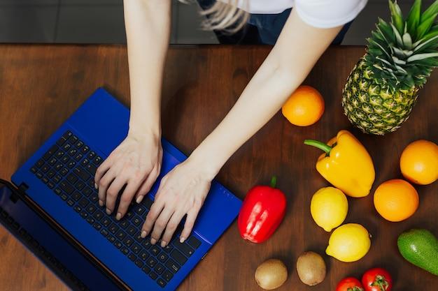 Vista dall'alto della donna utilizza il computer portatile per ordinare prodotti alimentari freschi in internet