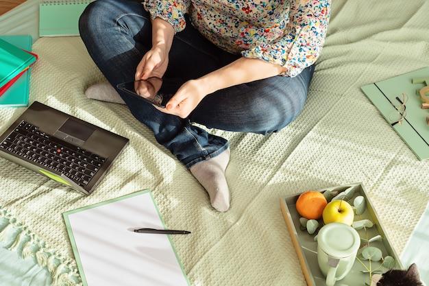 Vista dall'alto della donna che lavora in un ambiente informale con il suo laptop, blocco note, tazza di tè. lavoro a distanza, ufficio a casa, libero professionista, concetto di auto isolamento
