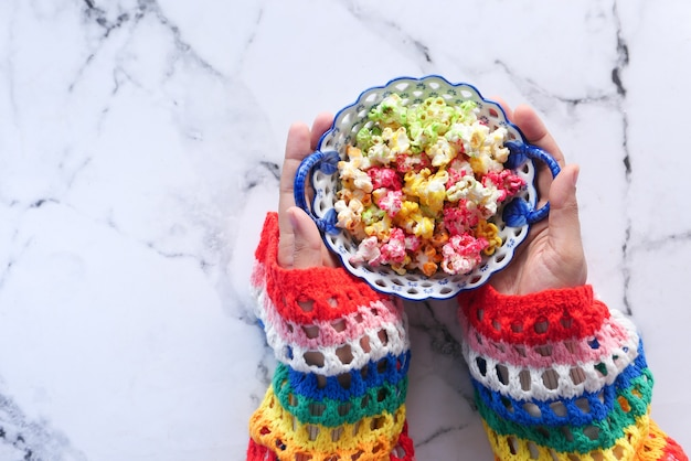 Vista dall'alto della mano delle donne che tiene una ciotola di popcorn colorati.