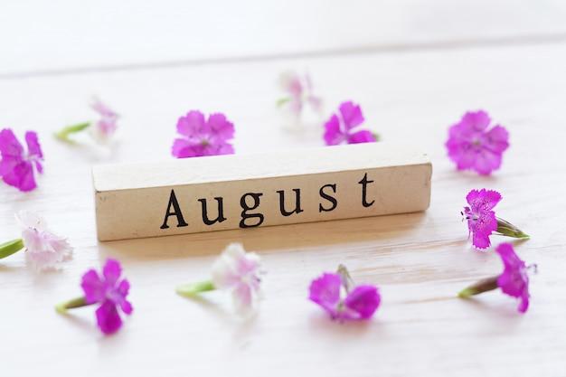 Vista dall'alto del calendario in legno con segno di agosto e fiori rosa.