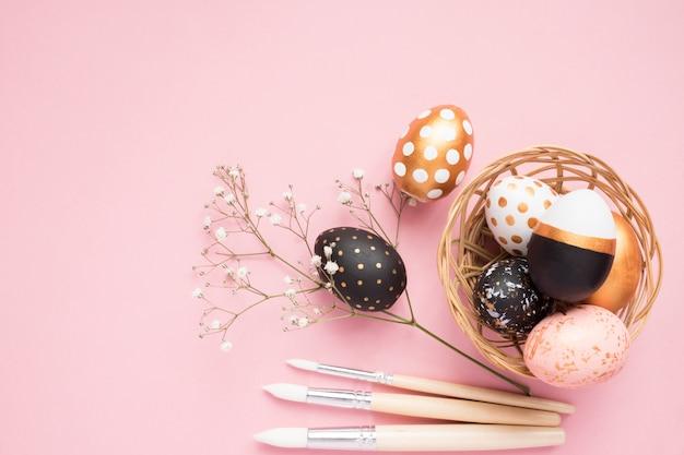 Vista dall'alto di uova dipinte in legno nei colori oro, nero e rosa con ramo di gypsophila e pennelli su sfondo rosa.