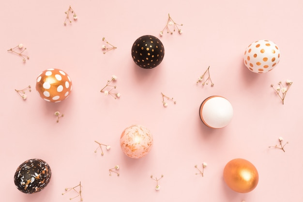 Vista dall'alto di uova dipinte in legno nei colori oro, nero e rosa con ramo di gypsophila su sfondo rosa. buona pasqua