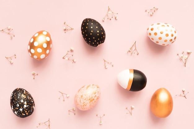 Vista dall'alto di uova dipinte in legno nei colori oro, nero e rosa con ramo di gypsophila sulla superficie rosa