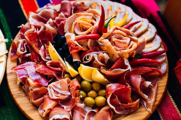 Vista dall'alto su un piatto di legno con fette di pancetta
