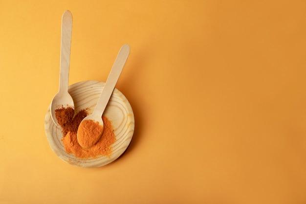 Vista dall'alto di piattini di legno con specie su uno sfondo arancione piatto.curcuma e callena in cucchiai di legno