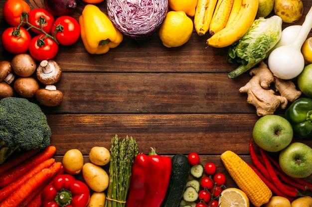 Vista dall'alto di un tavolo di legno pieno di frutta e verdura fresca