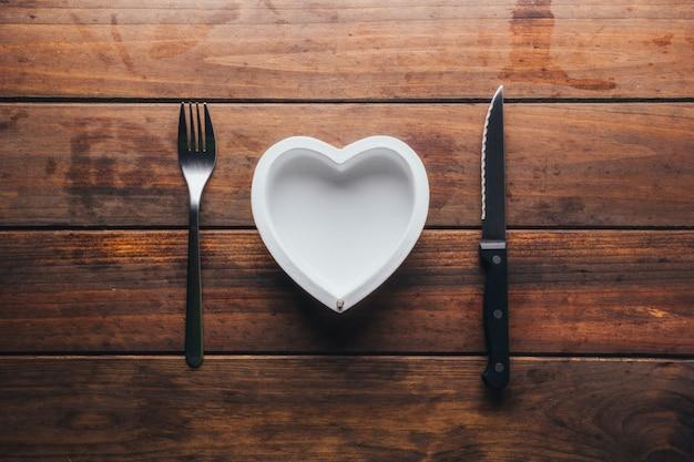 Vista dall'alto di un tavolo di legno con un piatto vuoto a forma di cuore e le sue posate