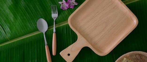 Vista dall'alto del vassoio in legno con cucchiaio e folk su foglia di banana
