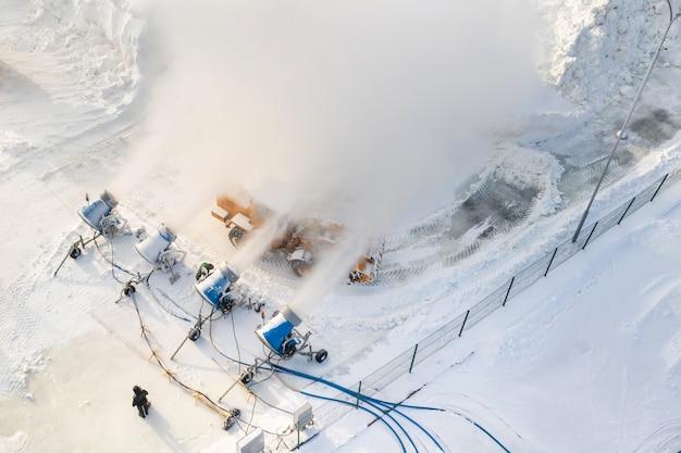 Vista dall'alto del lavoro di quattro cannoni da neve per la produzione di neve artificiale.