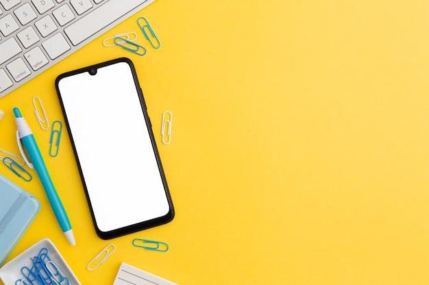 Composizione sul posto di lavoro di vista superiore su fondo giallo con lo spazio e il telefono della copia