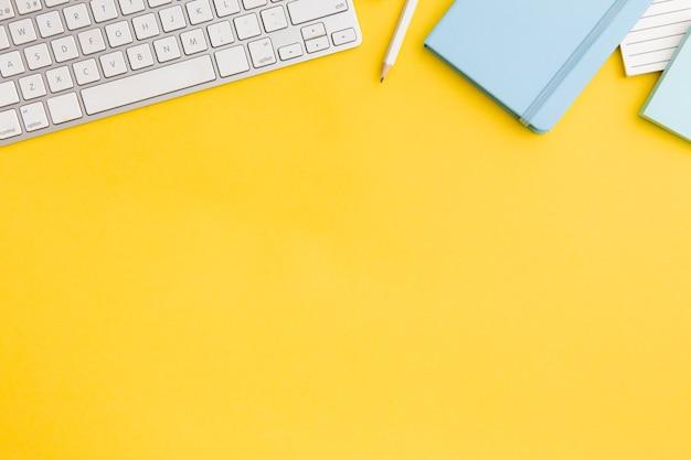 Composizione sul posto di lavoro di vista superiore su fondo giallo con lo spazio della copia