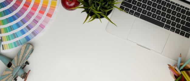 Vista dall'alto del posto di lavoro con copia spazio, laptop, forniture e decorazioni sul tavolo bianco