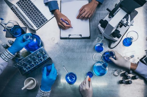 Area di lavoro vista dall'alto in laboratorio con strumenti per microscopio, laptop e laboratorio
