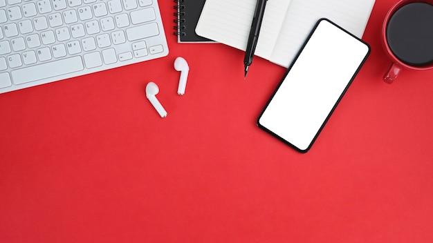 Area di lavoro vista dall'alto con schermo vuoto dello smartphone su forniture per ufficio creative sul tavolo rosso.
