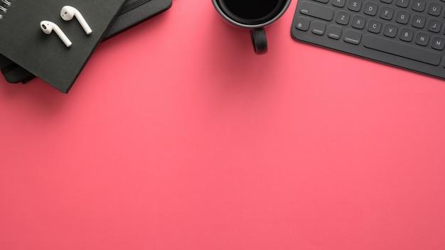Vista dall'alto dell'area di lavoro con tavoletta digitale, articoli per ufficio e copia spazio sul tavolo rosa