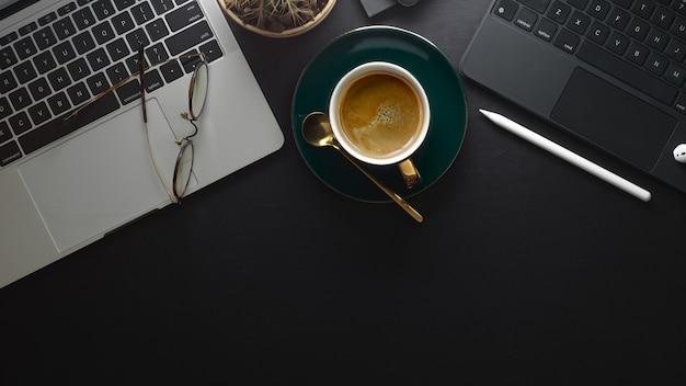 Vista dall'alto dell'area di lavoro con tastiere per laptop, occhiali, tazza di caffè e spazio di copia
