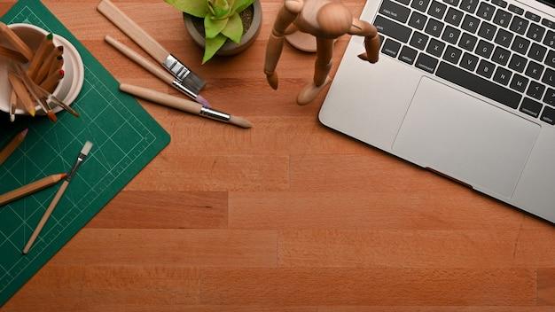 Vista dall'alto dell'area di lavoro con laptop, cancelleria, decorazioni e copia spazio sul tavolo di legno