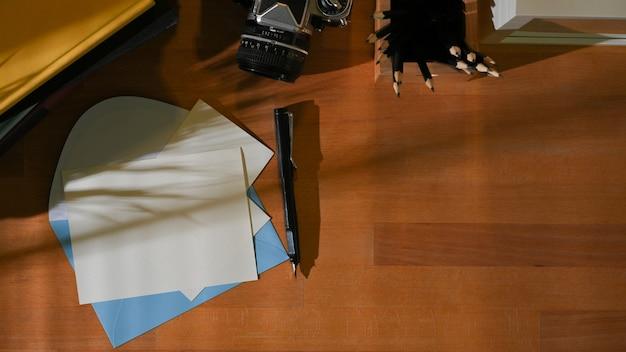 Vista dall'alto dell'area di lavoro con mock up card, buste, articoli di cancelleria e copia spazio nella stanza dell'home office