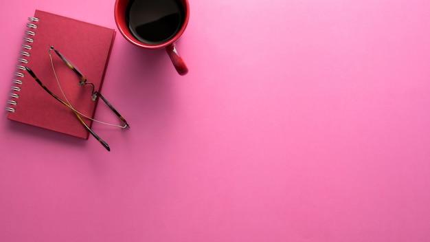 Vista dall'alto dell'area di lavoro con notebook, bicchieri, tazza di caffè e copia spazio sul tavolo rosa