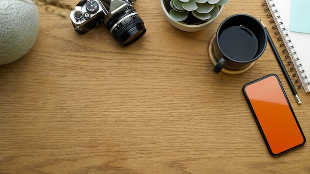 Vista dall'alto dell'area di lavoro con smartphone, tazza di caffè, fotocamera, cancelleria e copia spazio, spazio di lavoro piatto creativo