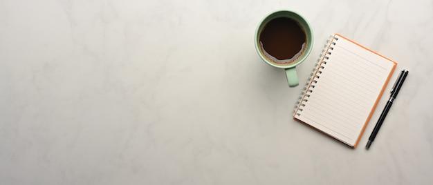 Vista dall'alto del piano di lavoro con taccuino, penna, tazza di caffè e copia spazio sulla scrivania in marmo