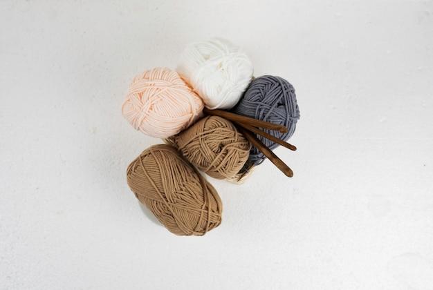 Vista dall'alto di gomitoli di lana e uncinetti in legno,