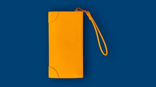 Vista dall'alto di un portafoglio da donna giallo su sfondo blu