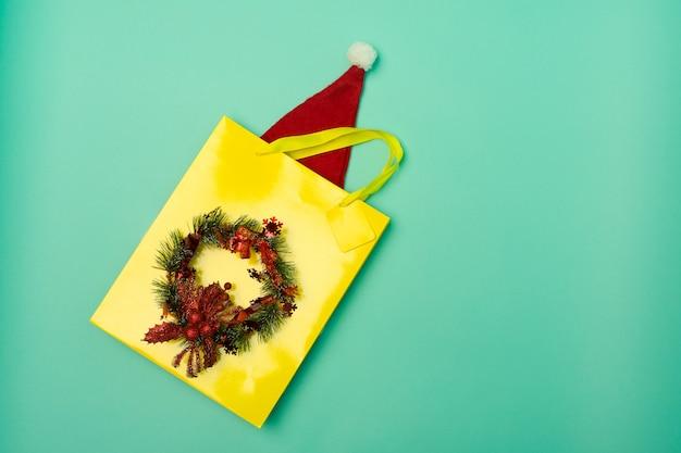 Borsa della spesa gialla vista dall'alto con cappello di babbo natale sul tavolo con le festività natalizie