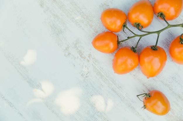 Vista dall'alto di pomodori gialli su un azzurro con copia spazio per il testo