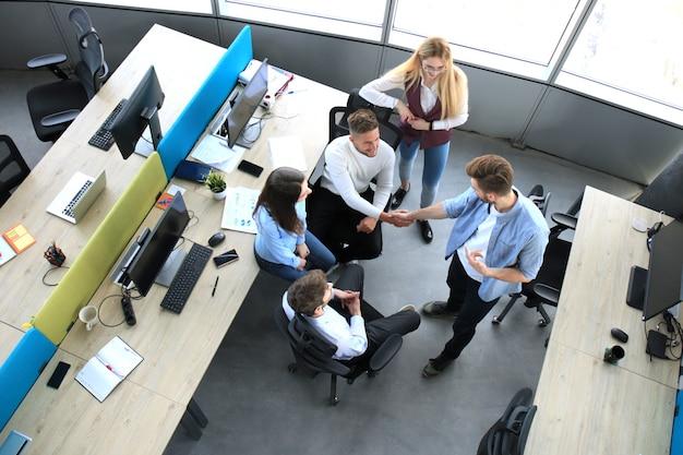 Vista dall'alto di giovani partner commerciali che si stringono la mano sull'affare in ufficio. concentrati sulla stretta di mano.