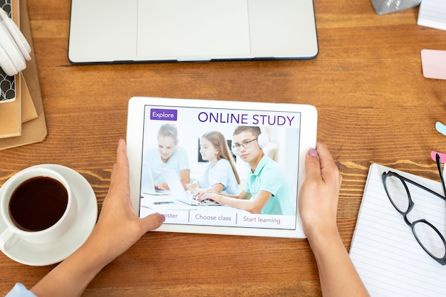 Vista dall'alto di giovani mani femminili che tengono il touchpad con la homepage del sito web educativo in mostra